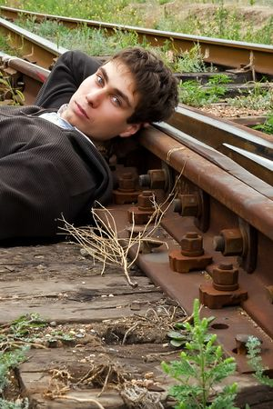 Young man laying on a railway tracks looking at you photo