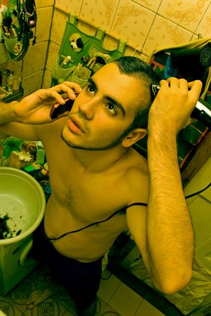 Young caucasian man shaving his head with electrical machine photo