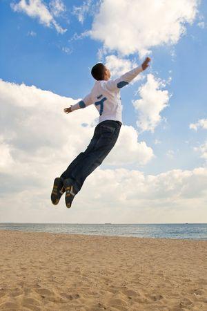 Jung Kerl jumping High am Strand, wie er in den Himmel fliegen ist  Standard-Bild - 5807316