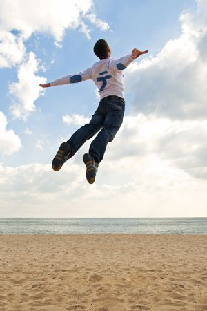 Young guy jumping high on the beach like he is flying into the sky