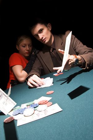 trickery: Young man throwing money on the table while playing cards
