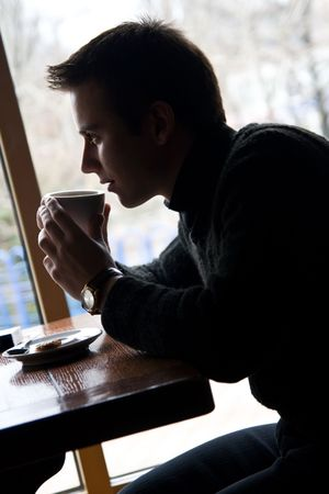 single man: Young guy drinks coffee at the window in a cafe