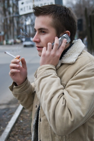 Young smoking man with a mobile phone and cigarette photo