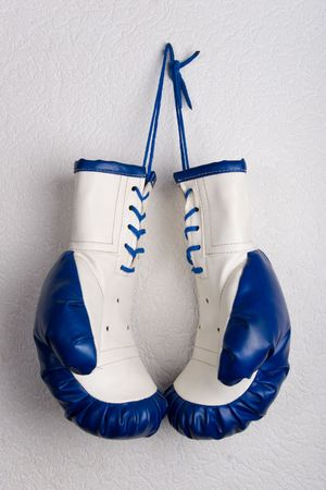 White and blue boxing gloves hanging on a wall photo