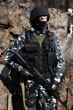 Armed officer in full ammunition with automatic russian rifle AK47 photo
