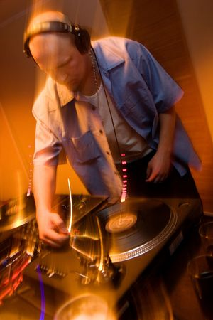 Deejay mixing vinyl records on a turntable players in blured motion photo