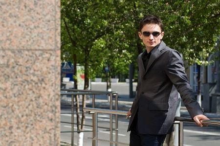 Young businessman in sunglasses leans on handrails photo