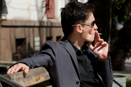 Smoking young man in sunglasses photo