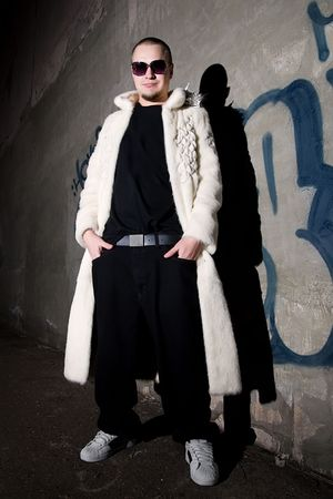 Man in long white fur coat posing like a pimp near the grungy  wall at night