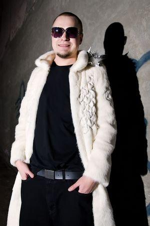 gigolo: Man in long white chinchilla fur coat posing like a pimp near the grungy  wall at night