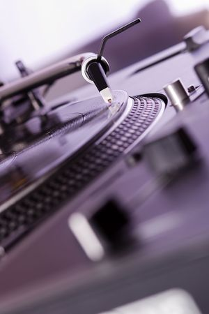 Turntable playing a record with music in the club photo