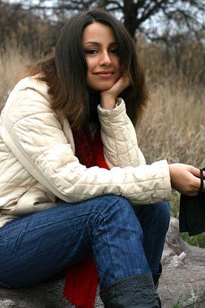 swarthy: Swarthy joyful chick in demi-season coat Stock Photo