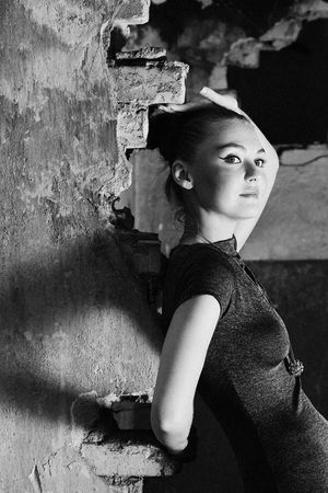 Attractive young lady posing somewhere in industrial ruins. Photo in monochrome. photo