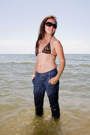 Girl stands in wet jeans in the water of a sea photo