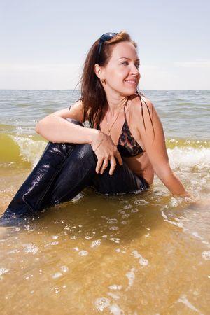 pantalones vaqueros mojados: Joven adulta en jeans h�medos se sienta en salpicaduras de marejadas de un sonriente de mar