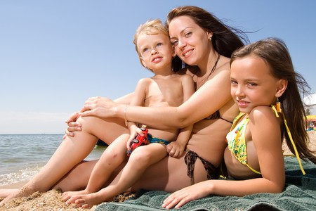 guy on beach: Mom and her children enjoying their vacation at the beach