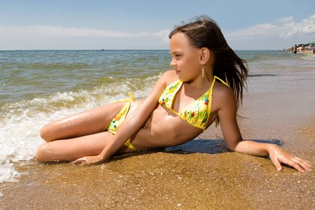 little girl posing: Little girl laying on the beach in water of a sea Stock Photo