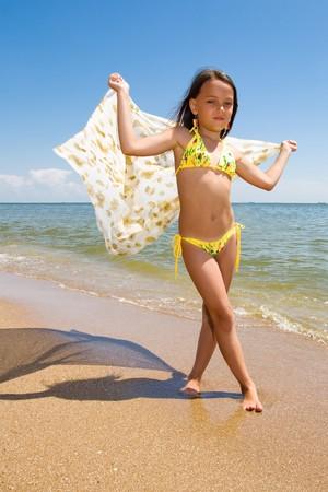 Small girl posing at the beach at day photo