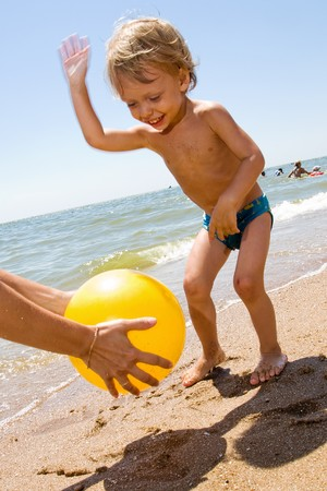 Infant kid plays ball at the sea photo