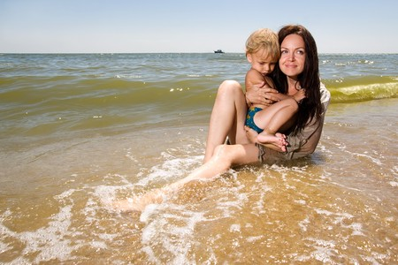 Young mom holds her little son in hands sitting in water of a sea photo