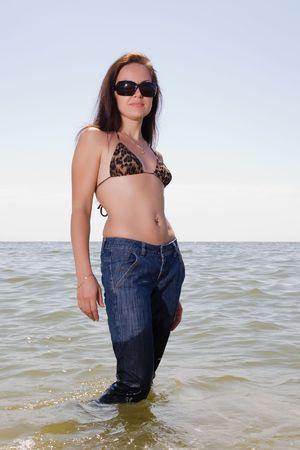 pantalones vaqueros mojados: Ni�a se encuentra en jeans h�medos en el agua de un mar  Foto de archivo