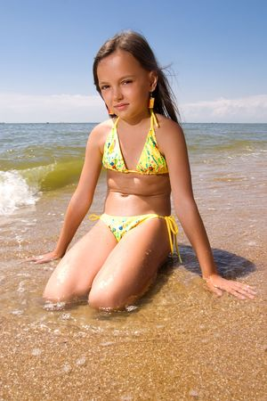 Little girl sitting in water of a sea at day photo
