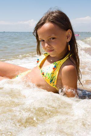 Kleine Mädchen, die Verlegung in wasserspritzer am Meer  Standard-Bild - 7357084