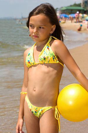 maillot de bain fille: Petite fille permanent avec un ballon sur le rivage de la mer