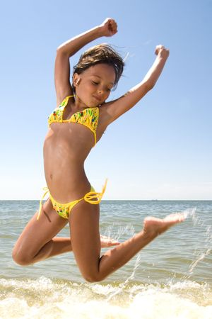little girl swimsuit: Little girl jumping high in water of a sea Stock Photo