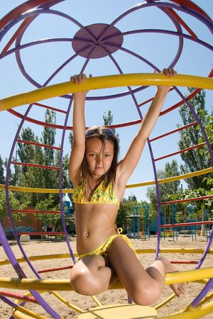 Little girl sitting at the playground on the sandy beach