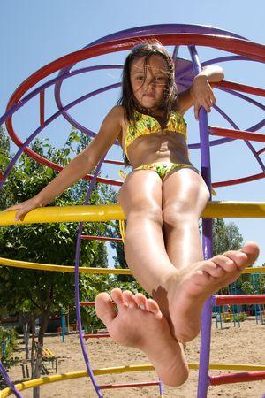 badpak: Meisje, zittend op de speel plaats op het zand strand