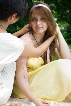 coverlet: Young brunette girl braiding her friend sitting in the coverlet outdoors at day Stock Photo