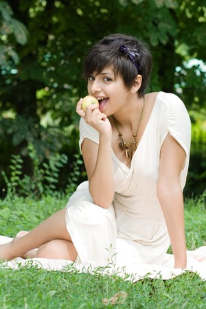 coverlet: Healthy and beautiful young woman eats an appla sitting on coverlet upon green grass
