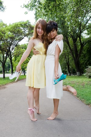 Copule of late teenage girls walking barefoot somewhere in the green park photo