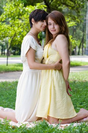 coverlet: Two girls chilling in the park on the coverlet upon green grass