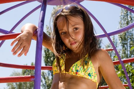 Little girl sitting at the playgorund at summer Stock Photo - 7375132