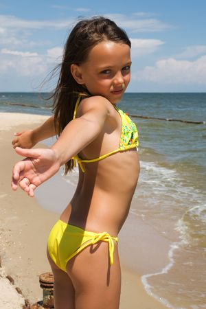 Small girl posing at the beach alone photo