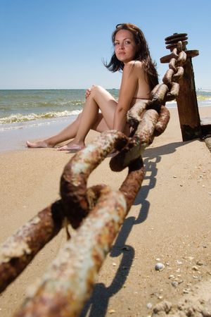 Young woman sitting at the seaside alone photo