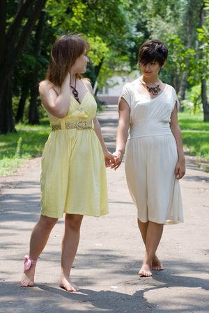 Two young attractive girls walking in the park barefoot with koined hands photo