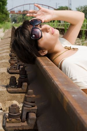 Young brunette girl laying on the railroad at day Stock Photo - 7375155