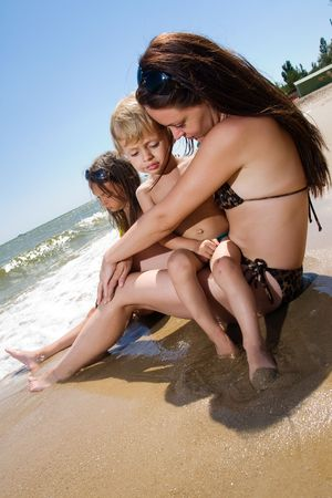 Mother and her kids sitting on the beach Stock Photo - 7375168