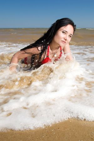 Pretty girl in water splashes at the seaside photo