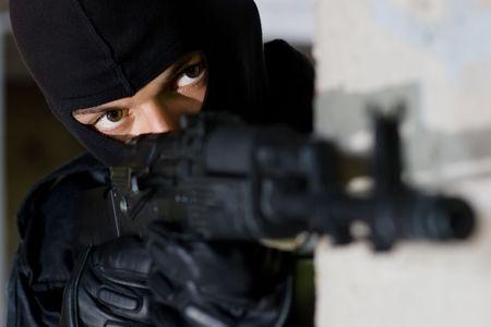 airsoft gun: Gunman aiming his target with an automatic russian AK-47 rifle