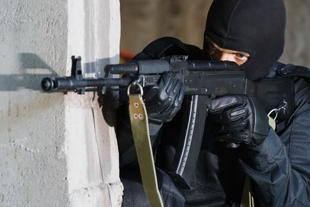 hideout: Gunman aiming his target with an automatic russian AK-47 rifle