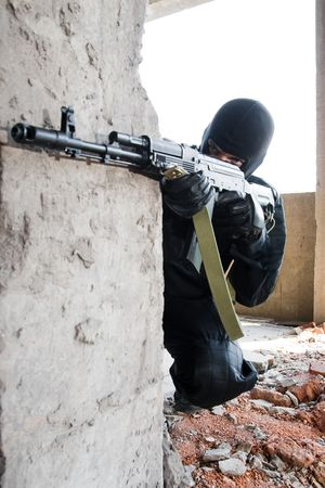 Man in black camouflage targeting with an AK-47 automatic rifle photo