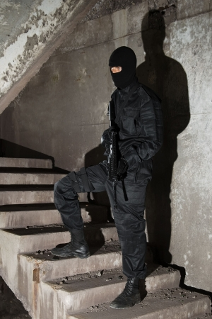 Man in black uniform holding M-16 rifle standing on stairs photo