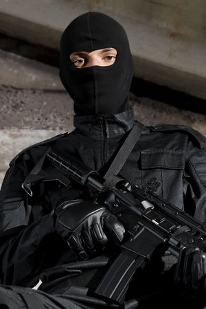 airsoft: Man in black uniform holding M-4 rifle