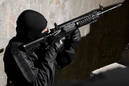 targeting: Man in black camouflage targeting with an automatic american M-4 rifle Stock Photo