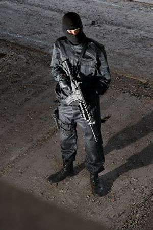 Trooper in black camouflage holding a gun photo