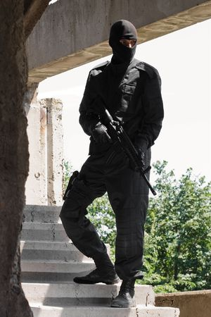 airsoft gun: Man in black uniform holding M-4 rifle